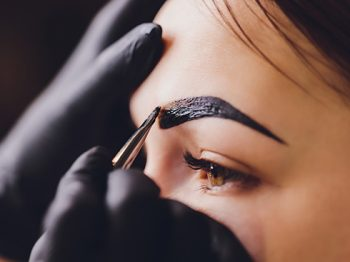 beautician- makeup artist applies paint henna on previously plucked, design, trimmed eyebrows in a beauty salon in the session correction. Professional care for face