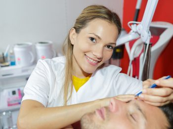 beautician giving epilation treatment to young man face